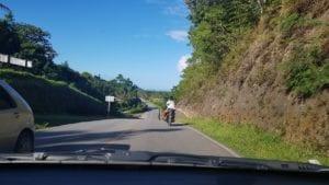 Moto com 2 passageiros, sem capacete em estrada sem acostamento - República Dominicana