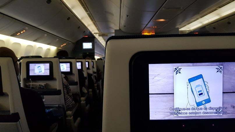 Dentro do avião, vendo as instruções de segurança antes da decolagem