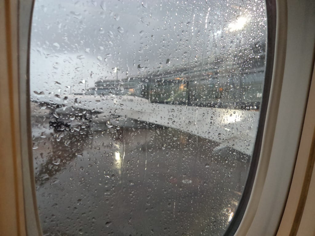Janela do avião antes do embarque em dia de chuva