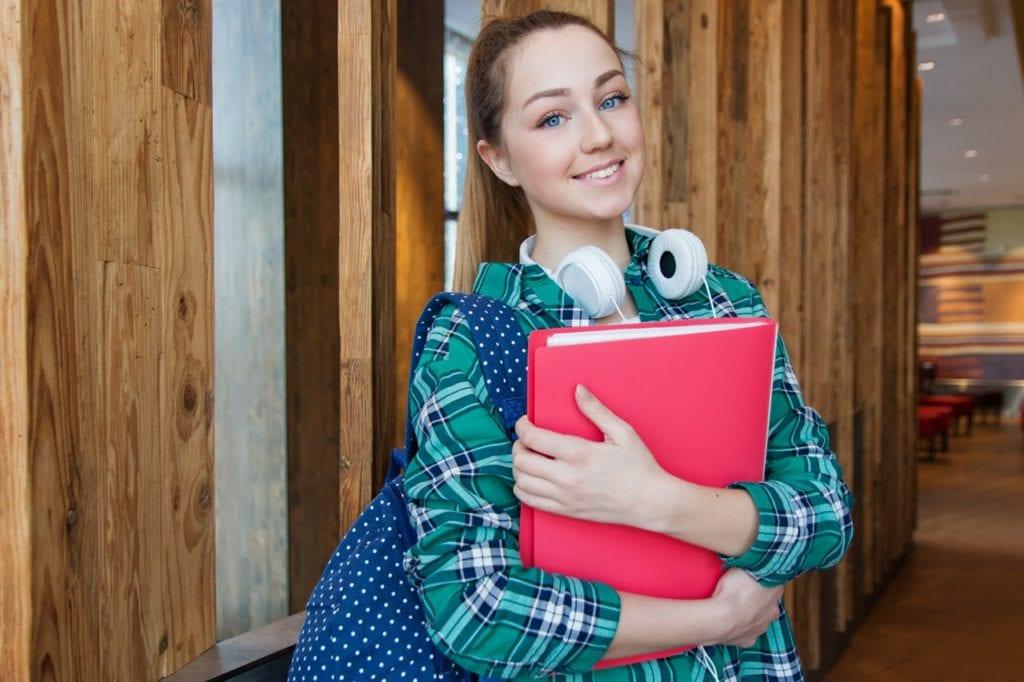 Jovem estudante segurando livros - Foto Pexels